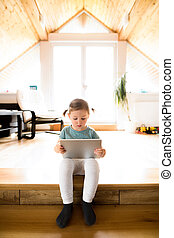 Little girl at home watching something on tablet.