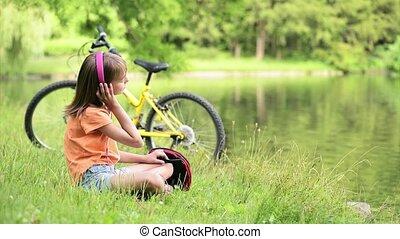 Little girl at lakeside - Little girl with headphones...