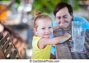 Little girl at outdoor restaurant