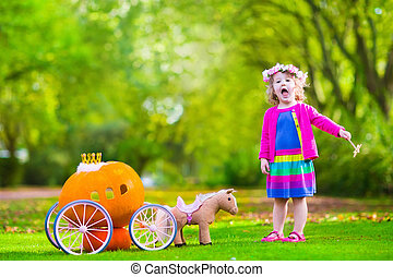 Little girl at pumpkin patch at Halloween - Cute curly...