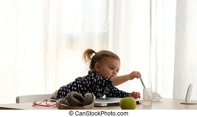Little girl at table with laptop