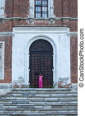 little girl at the huge metal doors to temple