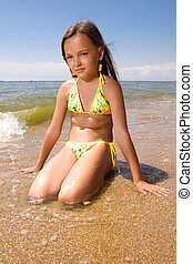Little girl at the seaside - Little girl sitting in water of...