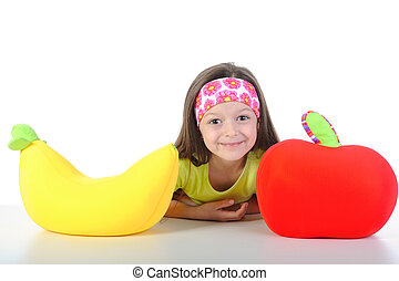 little girl at the table with a big banana and apple
