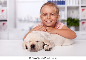 Little girl at the veterinary doctor with her puppy dog asleep on the examination table