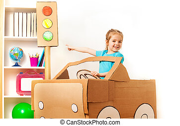 Little girl at the wheel of handmade cardboard car - Smiling...