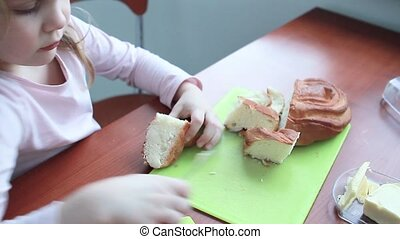 little girl baby smears butter on a loaf of bread - little...