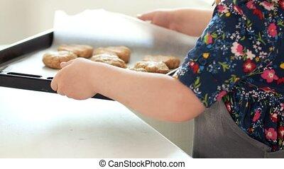 Little girl baker holding in hands baking sheet with...