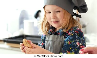 Little girl baker holding in hands homemade cookie