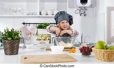 Little girl baker on kitchen puts eggs to the pastry dough for cooking biscuits