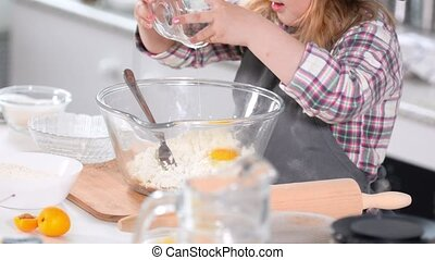 Little girl baker on kitchen puts eggs to the pastry dough...