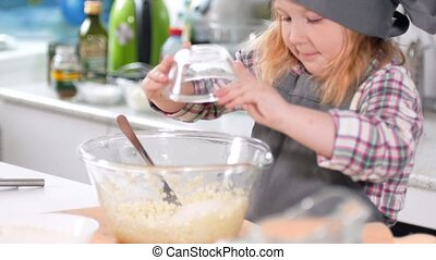 Little girl baker on kitchen puts sugar to the pastry dough for cooking biscuits