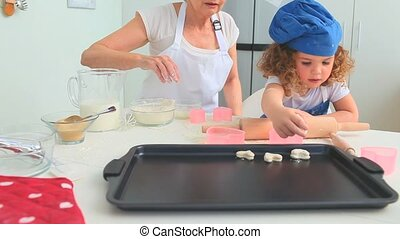 Little girl baking cookies with her grandmother in the...