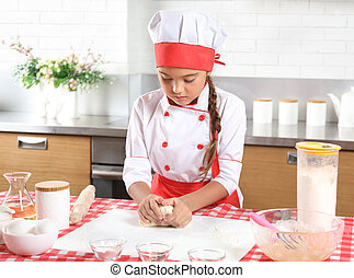 Little girl baking in the kitchen at home