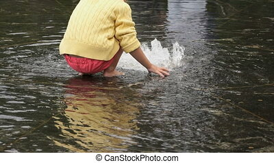 Little girl barefoot collects coins in fountain - Unknown...