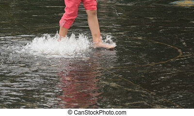 Little girl barefoot walking on fountain in summer - Unknown...