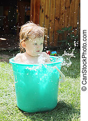 Little girl bathes in a bucket