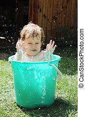 girl bathes in a bucket