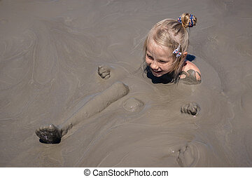Little girl bathes in a mud volcano on the sea shore.