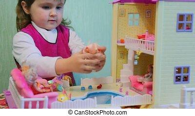 little girl bathes plastic doll