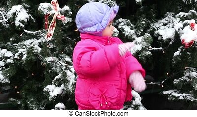 Little girl beat one hand to another in order to clean mittens, she stands in front of Christmas tree covered with snow