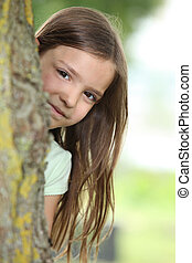 Little girl behind a tree