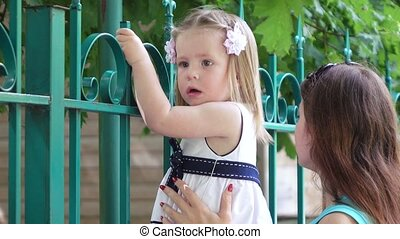 little girl behind the fence of the zoo