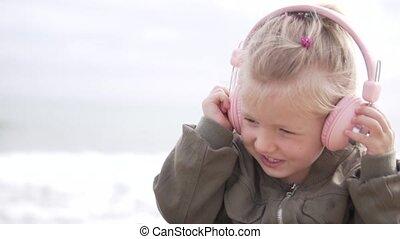 Little girl blonde listens to music on headphones.