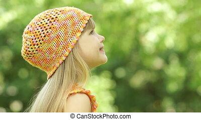 Little girl blowing a dandelion. Cl