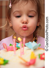 little girl blowing birthday candles, blur
