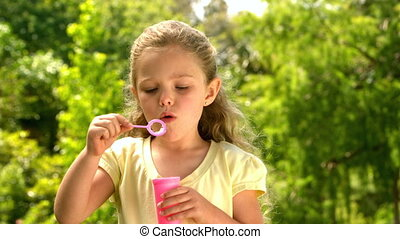 Little girl blowing bubbles