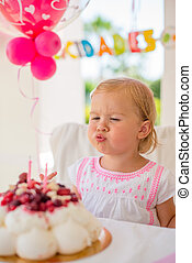 Little Girl Blowing Candles on Her Birthday Cake
