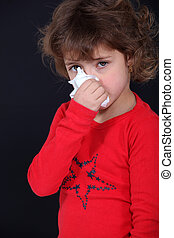 Little girl blowing her nose