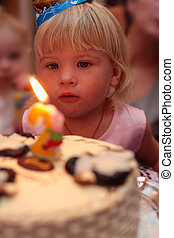little girl blowing on birthday cake