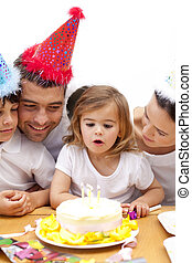 Little girl blowing out candles in her birthday\'s day with...