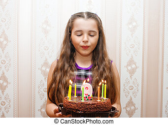 little girl blowing out candles on the cake