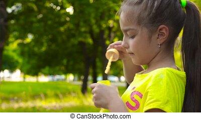 Little girl blowing soap bubbles in park. Closeup portrait -...