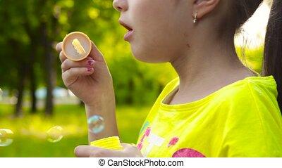 Little girl blowing soap bubbles in park. Closeup video -...
