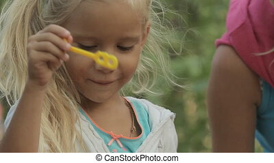 Little girl blowing soap bubbles in the forest