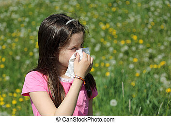 Little girl blows her nose with the handkerchief in the middle o