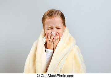 Little girl blows her nose, wrapped in a plaid, on a gray background