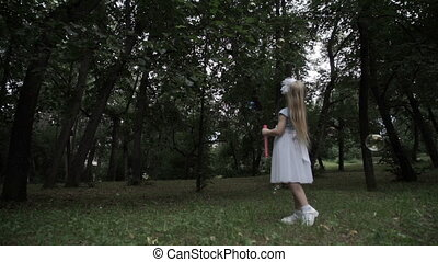 Little girl blows soap bubbles in the park
