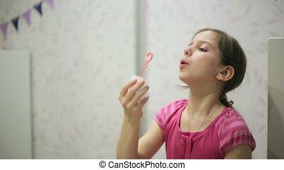 Little girl blows soap bubbles