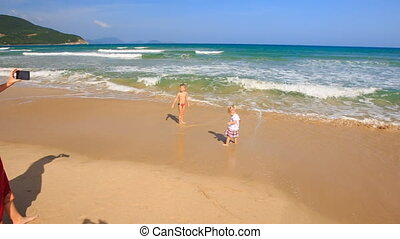 Little Girl Boy Play in Surf Mother in Red Photos