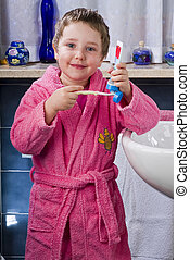 little girl brushes her teeth