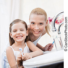 Little girl brushes teeth with her mom