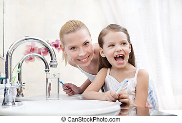 Little girl brushes teeth with her mother