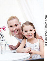 Little girl brushes teeth with her mum