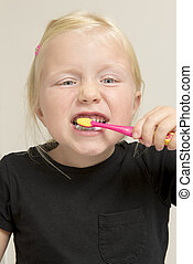 Little Girl Brushing Her Teeth with a Pink Toothbrush