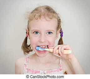 Little girl brushing her teeth with toothbrush.